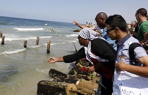 Des Palestiniens jettent des roses dans la mer Méditerranée, au large de la côte de Gaza, en signe de deuil après la disparition de réfugiés palestiniens à bord d'un bateau pour l'Europe qui a coulé au large de Malte, le 18 septembre 2014 - Photo : AFP/Mohammed Abed
